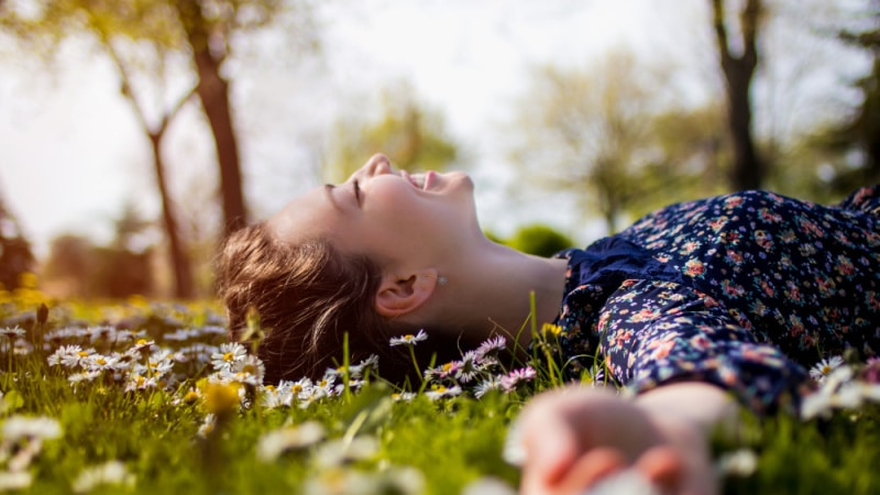 lady laying in the grass smiling - happy